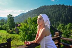 Young, beautiful, wrapped by a towel after a shower, a woman enjoys the first rays of the sun at dawn, standing on the balcony stock image