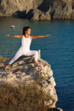 Young beautiful yoga girl doing exercises on the top of rocks at sea background. Royalty Free Stock Images