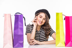 Young beautiful young woman with shopping bags on table satisfied and have rest with happy smile on white background Royalty Free Stock Images