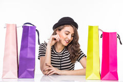 Young beautiful young woman with shopping bags on table satisfied and have rest with happy smile on white background Stock Photo