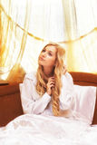 Young beautifulg blonde morning in the bed at morning. Young beautiful blonde in the bed at morning time near window under Sun rays Stock Photography