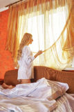 Young beautifulg blonde morning in the bed at morning. Young beautiful blonde in the bed at morning time near window under Sun rays Stock Image