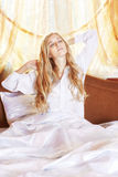 Young beautifulg blonde morning in the bed at morning. Young beautiful blonde in the bed at morning time stretching hands up with closed eyes Royalty Free Stock Image
