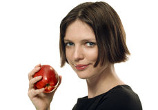 Young beautifull brunette taking an apple. Portrait of a young attractive woman with red apple on white royalty free stock photography