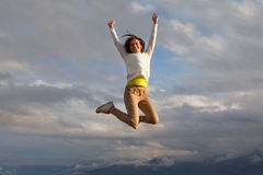 Young Beautifull Girl Oa A Peak Of A Mountait Jumping Royalty Free Stock Photo