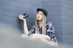 Young beautifull woman photographer is holding the camera. Young beautiful woman photographer is holding the camera and looking away. She has got long blond hair Royalty Free Stock Images