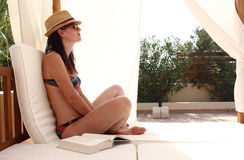 Young beautiful woman reads a book and relaxes over a pool bed close to the sea, Formentera, Spain Stock Image