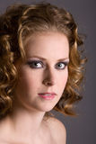 Young beauty. Beautiful young woman with curly blond hair on grey background Royalty Free Stock Images