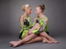 Young beauty acrobats sit and look aggressive Stock Photography