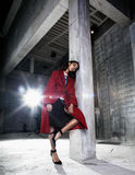 Young beauty african american woman in red coat  strange build. Ing, fashion look Royalty Free Stock Photos