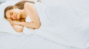 Young beauty asleep in a white bed.  Stock Images
