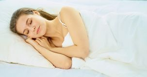 Young beauty asleep in a white bed.  Royalty Free Stock Images