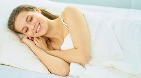 Young beauty asleep in a white bed.  Stock Image