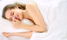 Young beauty asleep in a white bed.  Royalty Free Stock Photo