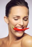 Young beauty biting red chili pepper royalty free stock image