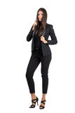 Young beauty in black formal suit posing while holding collar. Stock Photos