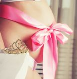 Young beauty blond pregnant woman at home, big belly. With ribbon like gift royalty free stock images