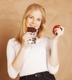 Young beauty blond teenage girl eating chocolate smiling, choice between sweet and apple Stock Photos