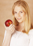 Young beauty blond teenage girl eating chocolate smiling, choice between sweet and apple Royalty Free Stock Images