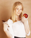Young beauty blond teenage girl eating chocolate smiling, choice between sweet and apple Stock Image