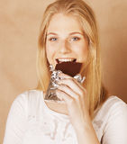 Young beauty blond teenage girl eating chocolate Stock Photo