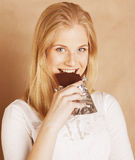 Young beauty blond teenage girl eating chocolate Royalty Free Stock Photography