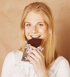 Young beauty blond teenage girl eating chocolate smiling Royalty Free Stock Photography