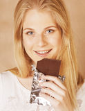 Young beauty blond teenage girl eating chocolate smiling Royalty Free Stock Photo