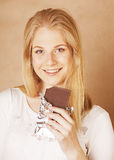 Young beauty blond teenage girl eating chocolate smiling Royalty Free Stock Photos