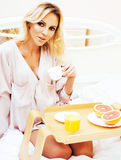 Young beauty blond woman having breakfast in bed early sunny mor Royalty Free Stock Photos