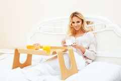 Young beauty blond woman having breakfast in bed early sunny mor Stock Photo