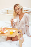 Young beauty blond woman having breakfast in bed early sunny morning, princess house interior room Royalty Free Stock Photography