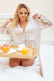 Young beauty blond woman having breakfast in bed early sunny morning, princess house interior room Stock Photo