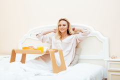 Young beauty blond woman having breakfast in bed early sunny morning, princess house interior room Stock Image