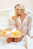 Young beauty blond woman having breakfast in bed early sunny morning, princess house interior room, healthy lifestyle Stock Images