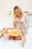 Young beauty blond woman having breakfast in bed early sunny morning, princess house interior room, healthy lifestyle Stock Photo