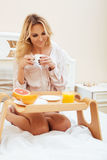 Young beauty blond woman having breakfast in bed early sunny morning, princess house interior room, healthy lifestyle Royalty Free Stock Photos