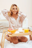 Young beauty blond woman having breakfast in bed early sunny morning, princess house interior room Stock Images
