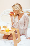 Young beauty blond woman having breakfast in bed early sunny morning, princess house interior room Stock Photos