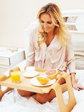Young beauty blond woman having breakfast in bed early sunny mor. Ning, princess house interior room, lifestyle people concept Royalty Free Stock Images