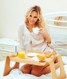 Young beauty blond woman having breakfast in bed early sunny mor. Ning, princess house interior room, lifestyle people concept Stock Image