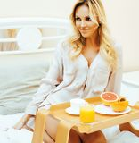 Young beauty blond woman having breakfast in bed early sunny mor. Ning, princess house interior room, lifestyle people concept Stock Photo