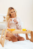 Young beauty blond woman having breakfast in bed early sunny morning, princess house interior room Royalty Free Stock Photo