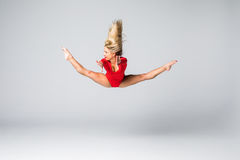 Young beauty blonde slim woman in red body jumping and doing gymnastic exercises on white background Royalty Free Stock Photography