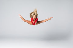 Young beauty blonde slim woman in red body jumping and doing gymnastic exercises on white background Royalty Free Stock Images
