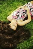 Young beauty brunette laying on the grass royalty free stock photos