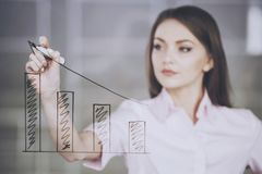 Young beauty businesswoman drawing a graph on glass screen in office.  royalty free stock photos