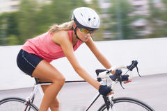 Young beauty caucasian professional cyclist on the move Stock Photography