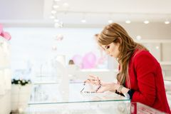 Young beauty elegance woman buying necklace. In jewelry store Royalty Free Stock Photos