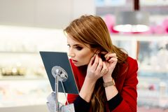 Young beauty elegance woman trying earrings in the jewelry store. Thoughtful woman in the store Royalty Free Stock Images